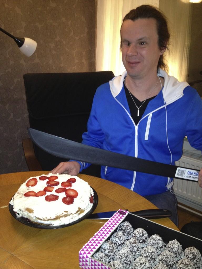 Bild: Joakim Nömell skär tårta med machete