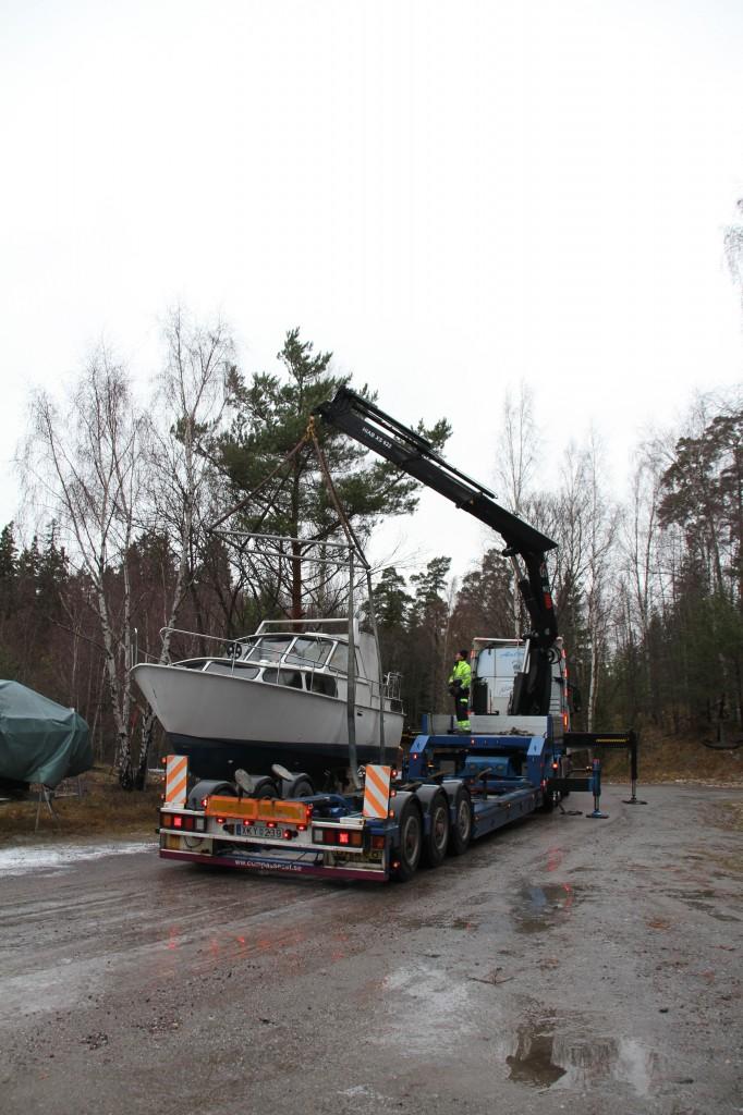 Bild: Lastbil med kran med båt bredvid