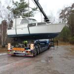 Bild: Båt hänger i kran över lastbilsflak, lite diagonalt