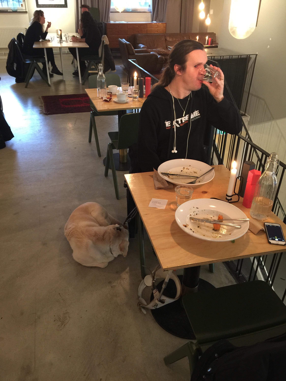 Bild: Joakim Nömell och ledarhunden Flinga vid restaurangbord