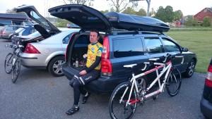 Bild: Joakim Nömell med ledartröja och cykel lutad mot bil