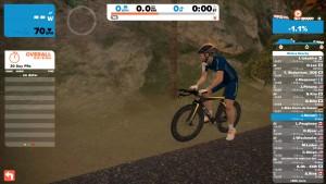 Bild: Zwift-cyklist med tempocykel och högprofilhjul vid vägkanten i Watopia