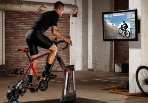 Bild: Wahoo Kickr Climb med monterad cykel och cyklist framför skärm